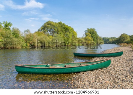 Two green canoes lying in river on the waterfront