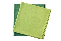 Two green folded textile napkins on white