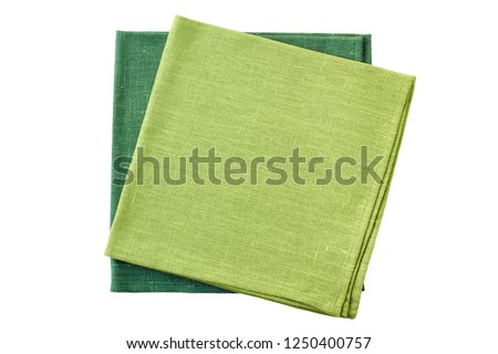 Two green folded textile napkins on white