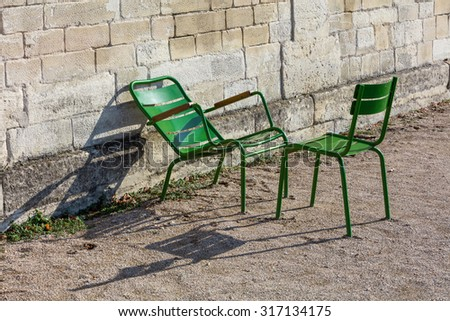 Two green garden chairs in the morning sunlight in the Tuileries Garden, Paris, France.