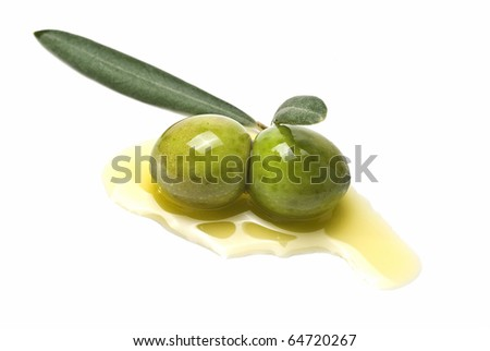Two green olives on some olive oil and isolated on a white background.