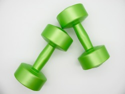 Two green plastic dumbbells of two kilograms for fitness lie next to each other on a white background
