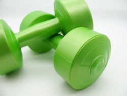 Two green plastic dumbbells of two kilograms for fitness lie on top of each other on a white background