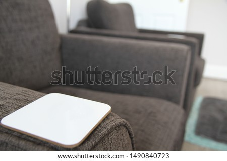 Two grey armchairs with white coaster on the arm