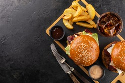 Two grilled hamburgers, French fries and a glass of cola with ice on a wooden board, ready to eat. Fast food background, copy space.