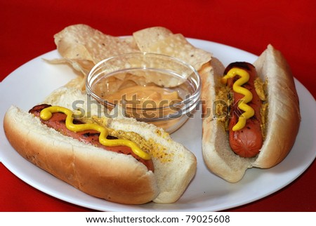 Two grilled hot dogs on white plate with chips and spicy cheese and jalapeno dip against red background.
