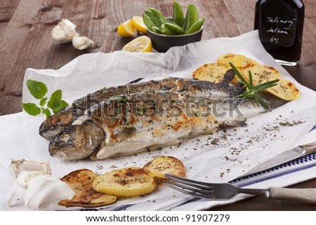 Two grilled trouts on white plate with lemon pieces, potatoes and balsamico on kitchen towel on wooden table.