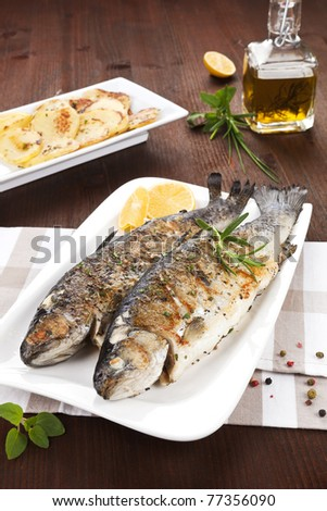 Two grilled trouts on white plate with lemon pieces, potatoes and olive oil on kitchen towel on wooden table.