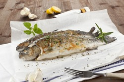 Two grilled trouts with lemon pieces, fresh herbs and garlic on white baking paper on kitchen towel on wooden table.