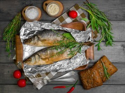 Two grilled whole fish trout on an aluminum foil on a gray wooden background. Additional ingredients for grilled fish greens rosemary, thyme, sage, tomatoes, salt, Fish sauce tartar. Top view.