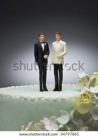 Two groom figurines on top of wedding cake - stock photo