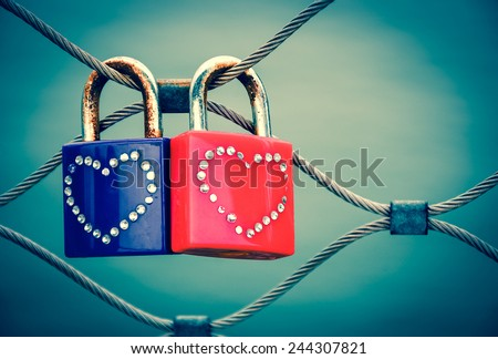 Two grungy love padlocks with heart decoration attached to the bridge in Paris. Valentine's day background. Toned photo.