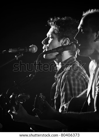 two guitar players singing and playing guitars on the stage, black and white image, for music,entrainment themes
