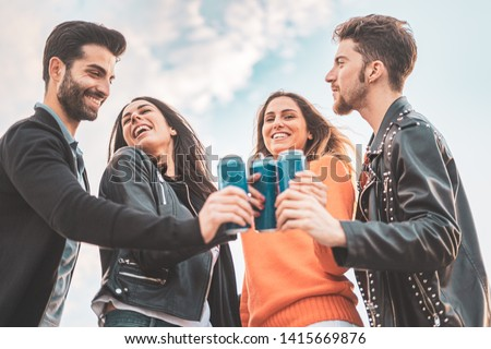 Two guys and two girls smiling and toasting with canned beers outdoor. Carefree youth having fun outdoors.