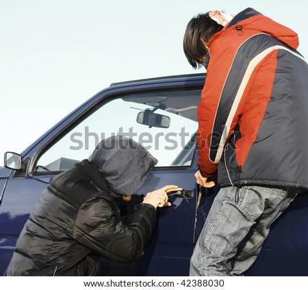 Two guys breaking door of a car