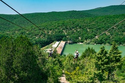 Two guys down a cable in a green valley. Rope descent with a carbine against the backdrop of a huge forest.