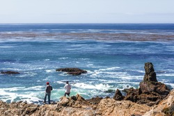 Two guys fishing, rock and geological formations along the rugged Big Sur coastline, near Monterey, CA. on the California Central Coast.