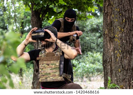 Two guys in a military kit. In the forest attacks from the back.