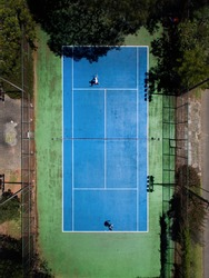 Two guys play tennis on blue tennis court