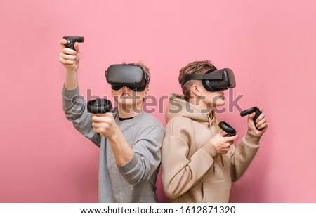 Two guys play VR games in virtual reality helmets on pink background, hold controllers and look away. Two friends in VR helmets play video games. Isolated. VR gaming with friends.