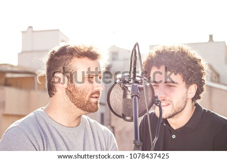 Two guys singing. Singing in the street, and one with Afro hair. Vintage photography and social networking #1078437425