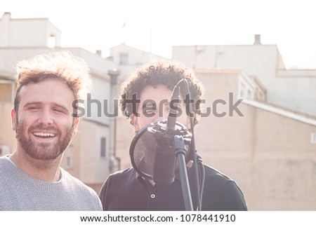 Two guys singing. Singing in the street, and one with Afro hair. Vintage photography and social networking #1078441910