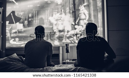 Two guys sitting at home on a sofa in front of a big screen. #1165421338