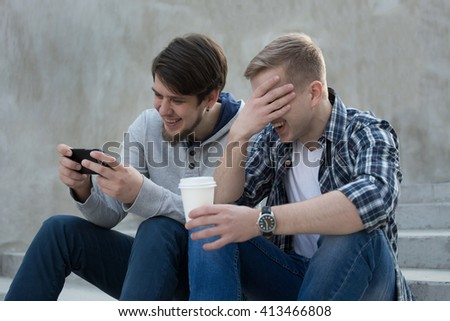 Two guys sitting on stairs with coffee, watch something in  smartphone and laugthing