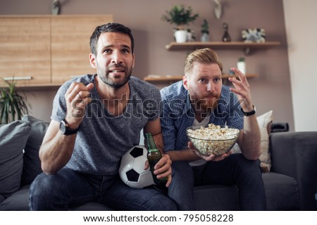 Two guys watching football game,drinking beer and eating popcorn at home. #795058228