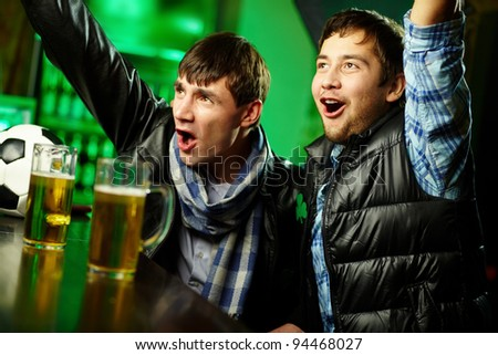 Two guys watching sports at bar and rejoicing