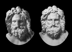 Two gypsum copy of antique statue Zeus head isolated on black background. Plaster sculpture man face with beard.