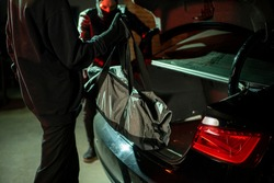 Two hackers putting bag into car-back after stealing digital media with data