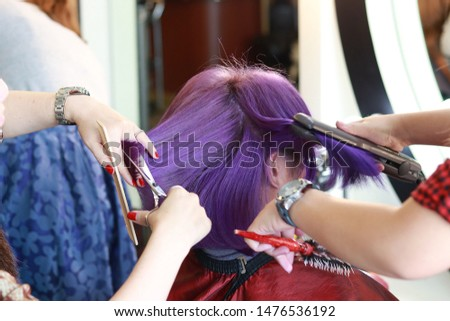 two hairdressers are service a violet short hair customer by cutting and ironing in salon