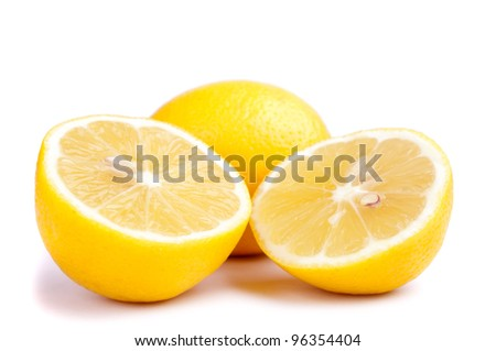 Two half an one whole lemons isolated on white
