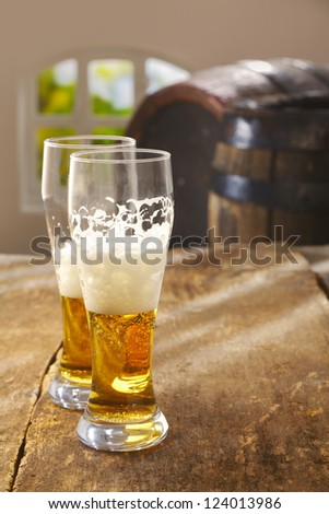 Two half drunk glasses of beer with a good frothy head standing on an old rustic wooden table with vintage wooden casks in the background