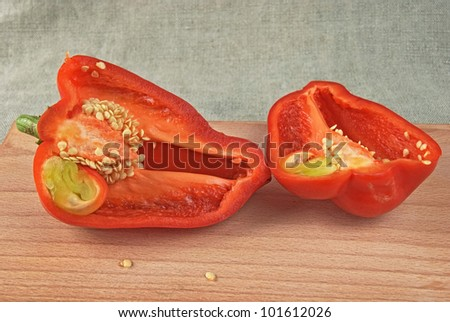 Two half of red sweet pepper on a wooden chopping board - stock photo