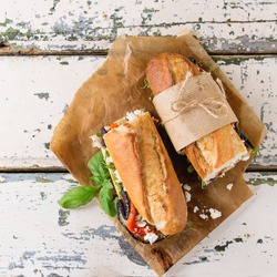 Two half of vegetarian baguette submarine sandwich with grilled eggplant, pepper and feta cheese served on baking paper over old white wooden background. Top view. Square image