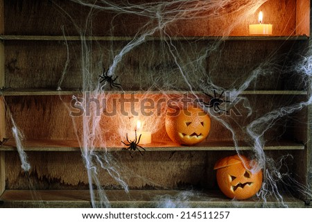 Two Halloween Jack o Lanterns Carved from Oranges and Spiderwebs with Spiders and Lit Candles on Shelves