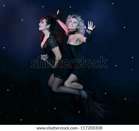two halloween witches flying on broom on a dark sky with stars