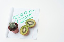 Two halves of kiwi fruit, cactus and paper with the caption