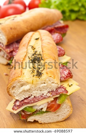 two halves of long baguette sandwich with lettuce, vegetables, salami and cheese on a wooden table and ingredients - stock photo