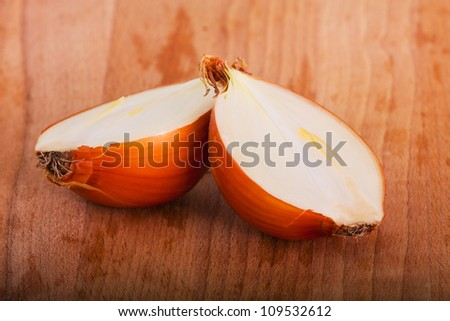 two halves of yellow onion on a wooden board