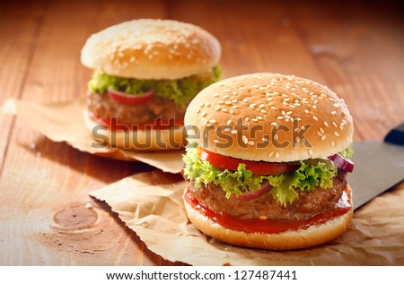Two hamburgers and french fries with sesame bun on brown paper