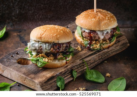 Two hamburgers with beef burger cutlet, fried onion, spinach, ketchup sauce and blue cheese in traditional buns, served on wood chopping board over dark wooden background.