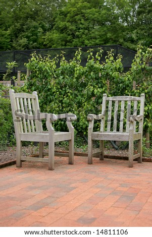 Two hand crafted oak wooden garden chairs standing on a terracotta tiled patio, with plants and trees to the rear.