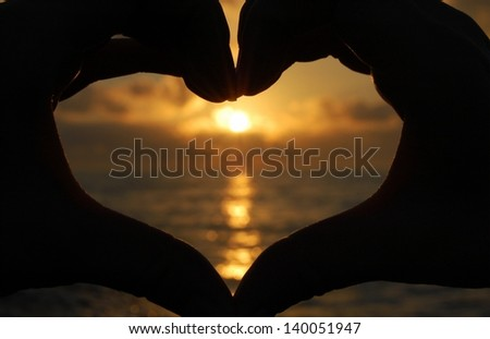 Two hand forming a heart shape symbol at sunset