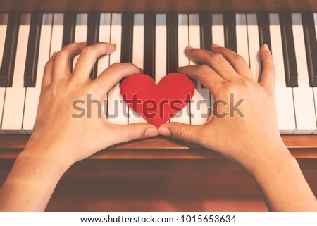 Two hand hold red cartoon heart on keyboard's piano, To tell love to learn music or to tell someone love. #1015653634