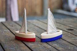 Two handcrafted wooden sailing boats. Handmade natural material toys for kids. Waldorf plaything ship. Red and blue tiny yachts