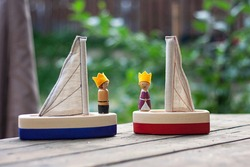 Two handcrafted wooden sailing boats with small figures of the king and queen with felt crowns. Handmade toys for kids. Waldorf plaything ship