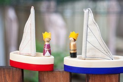 Two handcrafted wooden sailing boats with small peg dolls of the king and queen with felt crowns. Handmade play set for kids. Waldorf plaything ship